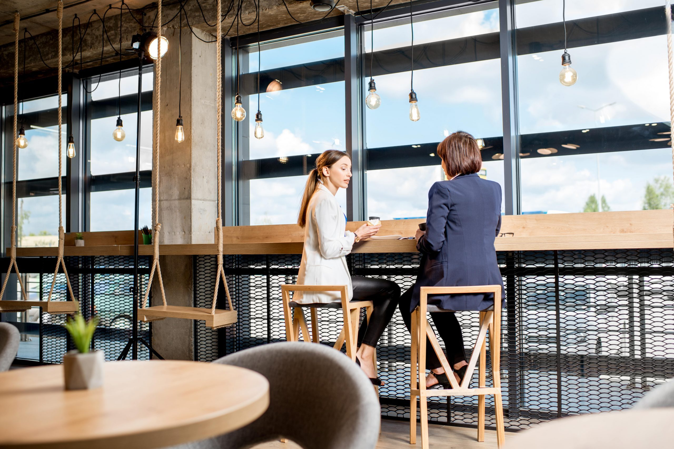 Two business women sitting during a coffee time near the window in the modern cafe interior